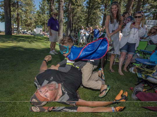 Larry The Cable Guy wrestles with 3  1/2 year old fan Xander Cliff Marshall during the American Century Championship at Edgewood Tahoe Golf Course in Stateline on Sunday.