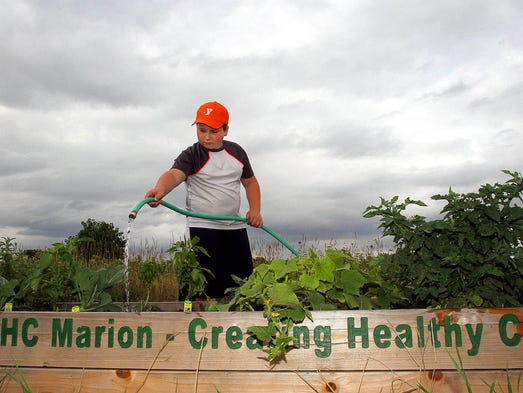 Hayden Branhan, 9, waters one of the raised beds where kids are growing vegetables in a community garden growing behind the Marion YMCA building.