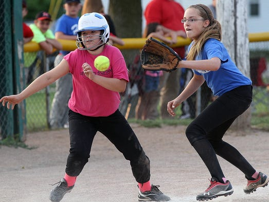 Skylah Rose (left) sprints for home as third baseman Autumn Rawlins awaits the throw on a run down play during the girl's 12U softball all-star game held at Lincoln Park on Wednesday, Aug. 6, 2014. The Merchants Baseball Club and the Knockouts Softball Club held their all-star games to cap off the 2014 summer season. James Miller/The Marion Star