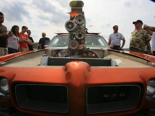 Muscle cars have been around for decades and customizers are always looking to make their cars go faster. A crowd gathers around Bill Bolin's 1970 Pontiac GTO parked in Royal Oak, Mich., in 2006
