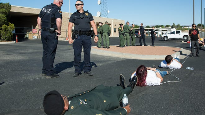 New Mexico Comunidades en Accion y de Fé lead a civil disobedience action during a protest in front of the Border Patrol station in Las Cruces, Thursday May 4, 2017. During the action members of CAFé blocked all the entrances and exits to the Border Patrol parking facilities.
