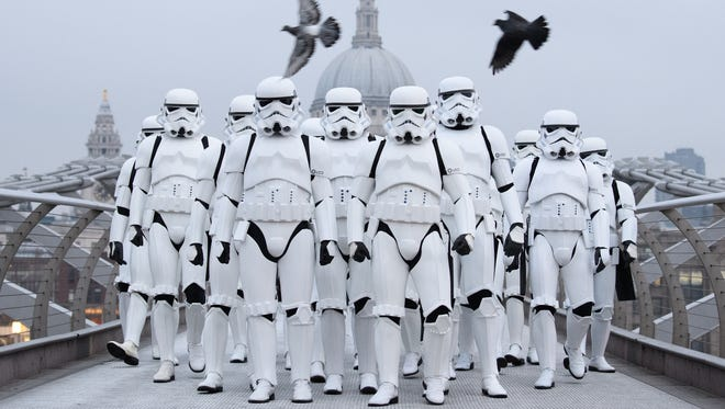"""People dressed as Stormtroopers from the Star Wars franchise of films pose on the Millennium Bridge to promote the latest release in the series, """"Rogue One"""" in London."""