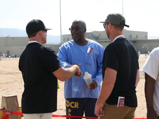 Inmate Jessie Lee speaks with fellowship volunteers Eric Duell, left, and Matt Gersonde during the Operation Starting Line at Salinas Valley State Prison on Friday