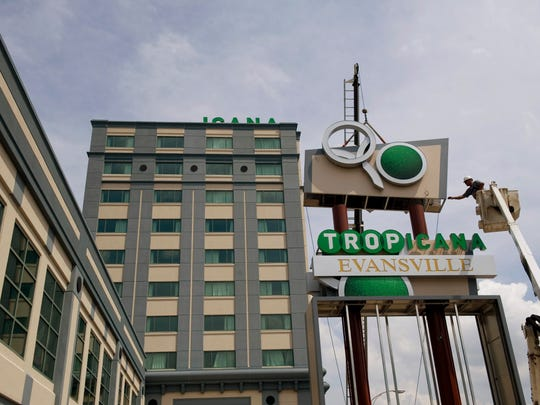 Hank's Signs employee Steve Campbell guides into place the uppermost piece of the new puzzle that is the sign for Tropicana Evansville - formerly Casino Aztar in Downtown Evansville - Wednesday afternoon.