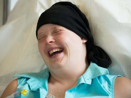 Katie laughs after making a series of goofy faces during her chemotherapy.
