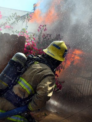 Firefighter starts attack on fire burning South Taft home.