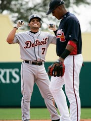 Tigers catcher Pudge Rodriguez, left, hits a double in the third inning against the Braves in spring training action in 2008 at Champion Stadium in Kissimmee, Fla.