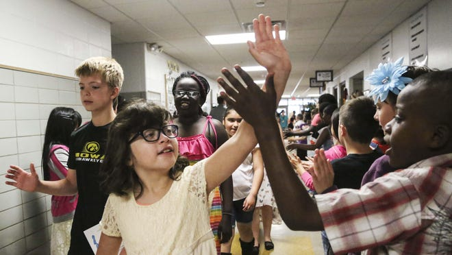 Kelly Morales, fifth grader at Garton Elementary reaches to give a teacher a high five during the annual clap out for fifth grade students as they graduate to middle school on the last day of the school, Monday, June 1, 2015 in Des Moines. Parents and younger students line the halls to clap and cheer for the fifth graders as they walk through the halls to mark the occasion.