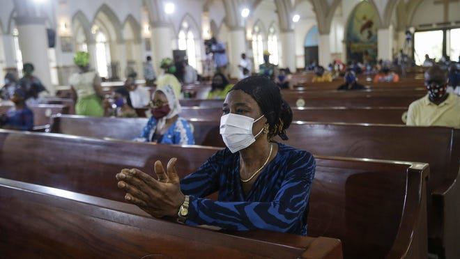 A churchgoer wears a face mask and practices social-distancing to curb the spread of the coronavirus during a Sunday Mass at the Holy Cross Cathedral in Lagos, Nigeria, Sunday, Aug. 30, 2020. The COVID-19 pandemic is testing the patience of some religious leaders across Africa who worry they will lose followers, and funding, as restrictions on gatherings continue.