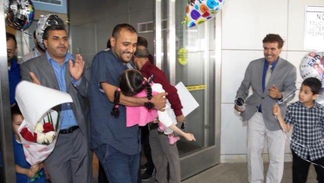 Nageeb Alomari carries his 11-year-old daughter Shaema Alomari after landing in New York.