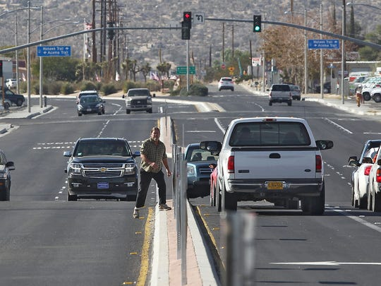 A man jaywalks across Highway 62 in the heart of Yucca Valley on Tuesday, November 11, 2014.