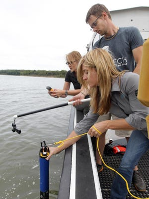 Tiffany Schirmer, of YSI Inc., lowers a device with multiple water quality sensors into the river.