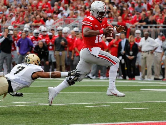 Ohio State quarterback J.T. Barrett, right, scores