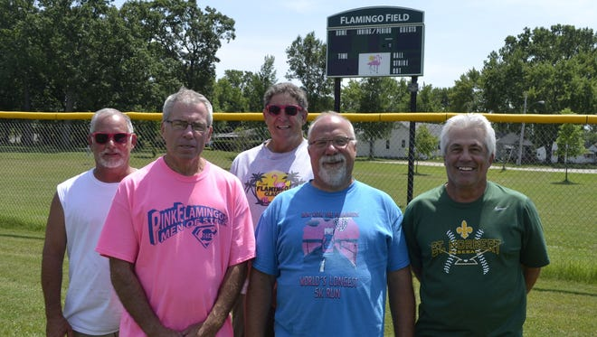 From left, longtime Pink Flamingo Classic organizers David Vande Hei, Dan McInnis, Jerry Olmsted, Charlie Kazik and Mike Mason stand in the outfield of the newly named Flamingo Field at Legion Park in De Pere. The city will dedicate the field Friday night, the first day of the 33rd annual Pink Flamingo softball tournament.