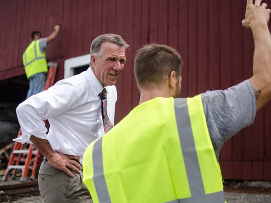 Gov. Phil Scott speaks with Thomas Savard, of Winooski,