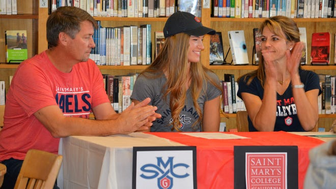 South Salem volleyball standout Selbie Christensen (center) is joined by her parents, Jeff and Wendi Christensen, during a college signing ceremony at South Salem High School on Nov. 16, 2017.