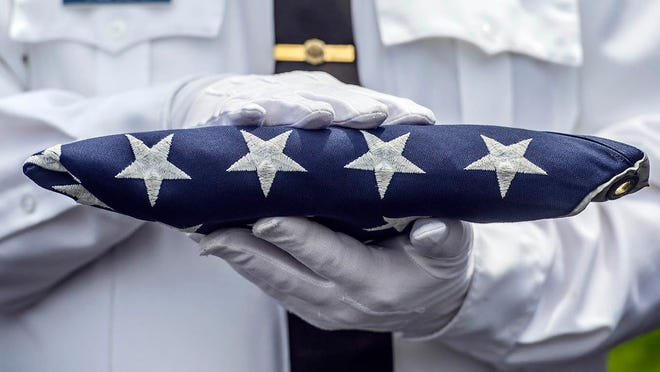 An honor guard member holds the American flag.