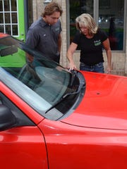 Karen Wielkopolan and her son John take a look at the used Hyundai Accent their business the Downtown Garage will be giving away to a needy family.