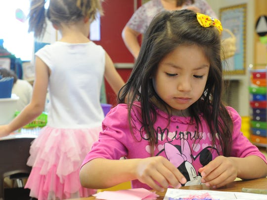 Mimi Mejia-Lazo glues pink papers to a drawing of a flower in a kindergarten class at Maple School in Thousand Oaks.