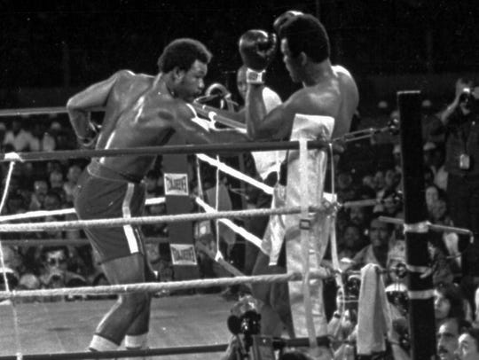 George Foreman attacks Muhammad Ali against the ropes,