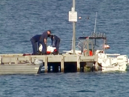 In this image taken from video, police carry a body in a bag and place it in on a stretcher on a jetty in Triabunna, off the Australian island state of Tasmania, on Saturday, July 25, 2015.