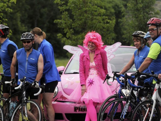 """The 2014 """"Breast Fairy"""" Laura Gordon takes pictures with bike riders before the Century Bike Ride benefit last year. Each year, the ride raises money for Cumberland Valley Breast Cancer Alliance and Rhonda Brake Shreiner Women's Center, Chambersburg."""