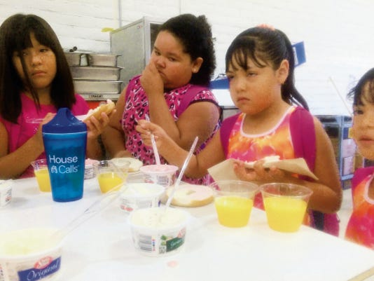 """Bill Armendariz — Headlight Photo   Bell Elementary School held its annual """"Bagels for Grandparents"""" event Friday morning in the school's gymnasium. Grandparents and students were treated to a variety of flavored bagels and a flavored cream cheese. Bell students, from left, Ymari Ramirez, Bani Nunez, Evelyn Vaszquez and Danerie Vasquez served many of the bagels to their guests."""