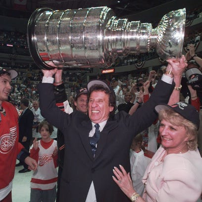 Red Wings owner Mike Ilitch, center, hoists the Stanley