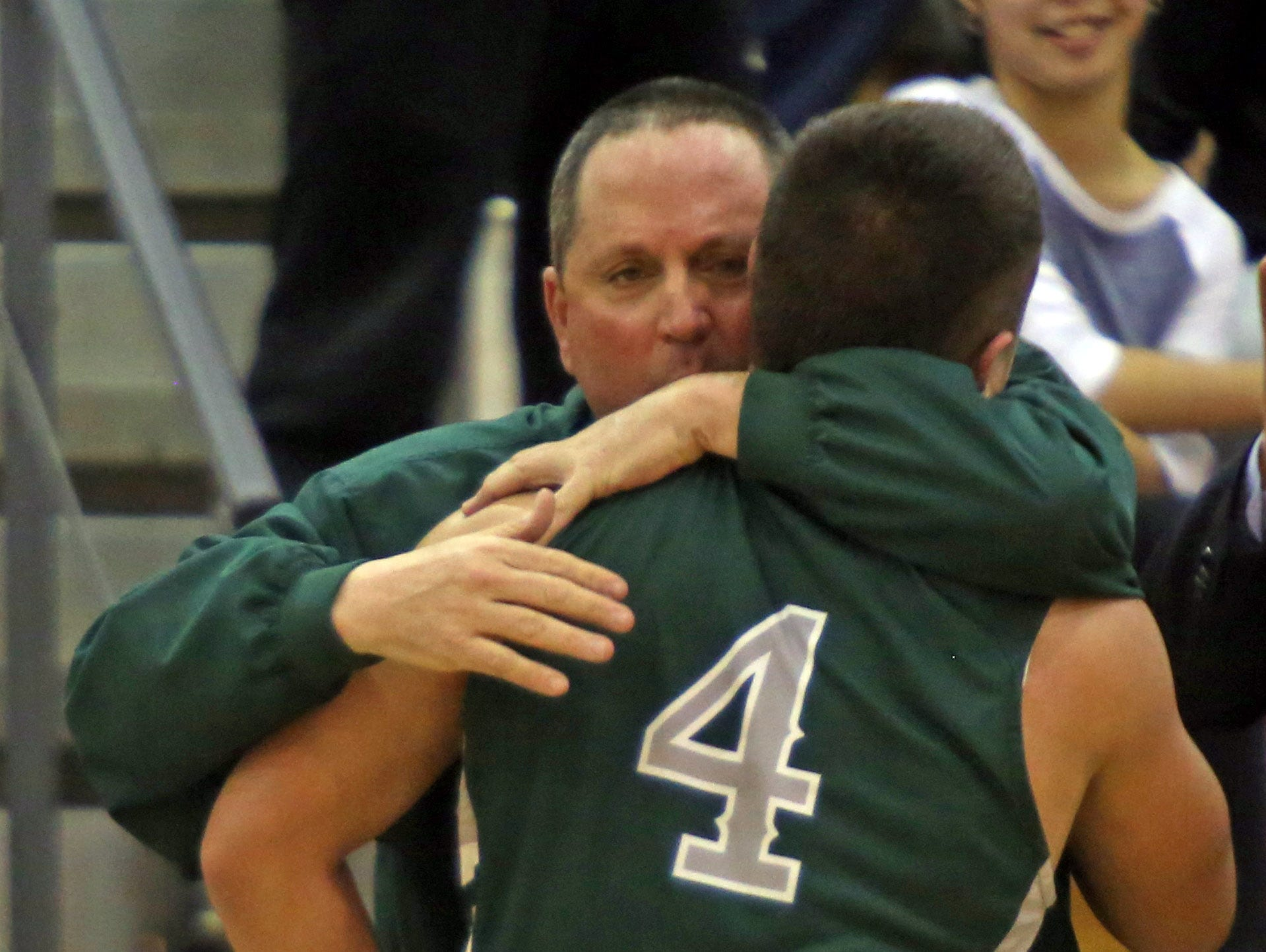Spackenkill coach Tom Bell hugs Camron Abalos (4) after their 69-50 victory over Pleasantville 69-50 in Class B State Regional semifinals at Yorktown High School March 7, 2017.