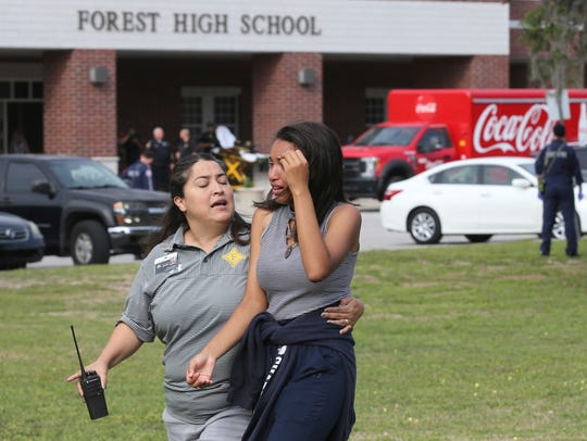 A student is comforted by a school official as students