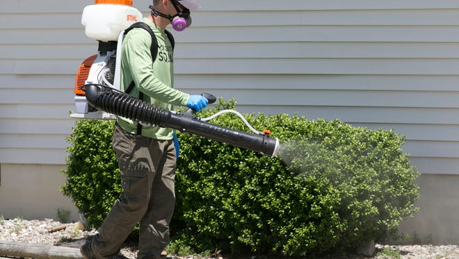 Adam Leighton, Berkeley, an applicator at a new pest control company called Mosquito Squad, sprays a house in Berkeley for mosquitoes.
