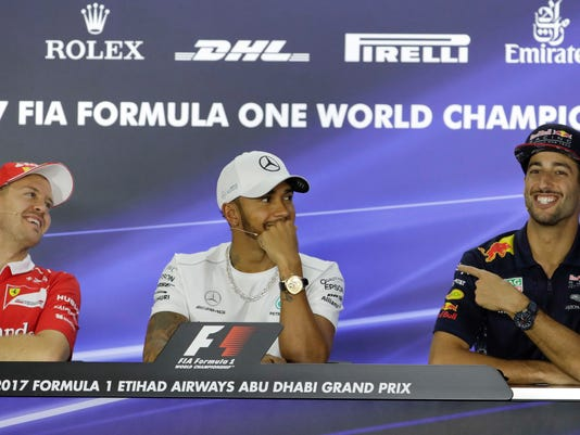 From left, Ferrari driver Sebastian Vettel of Germany, Mercedes driver Lewis Hamilton of Britain, and Red Bull driver Daniel Ricciardo of Australia share a light moment during a news conference at the Yas Marina racetrack in Abu Dhabi, United Arab Emirates, Thursday, Nov. 23, 2017. The Emirates Formula One Grand Prix will take place on Sunday. (AP Photo/Luca Bruno)