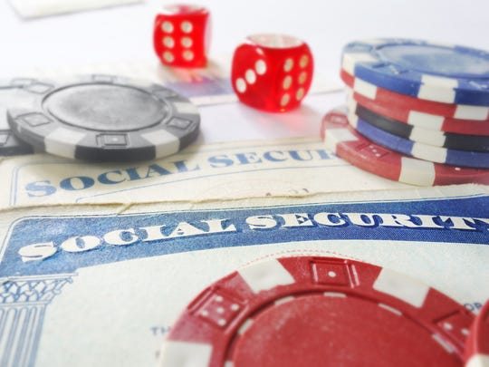 Red dice and casino chips are on top of two social security cards.