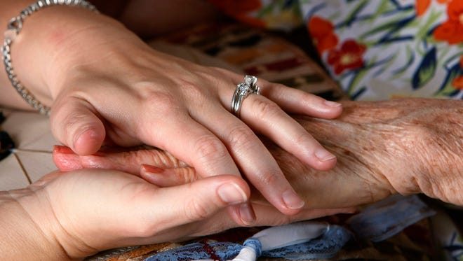 Rebekah Wilson, with Hospice of the Valley, holds the hand of a dementia patient who receives in-home care at her home in Mesa, Ariz.