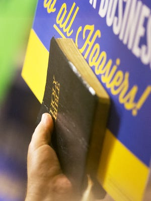 An opponent of SB 101, holds a bible during meeting of an Indiana House committee to discuss the merits of Senate Bill 101, the Religious Freedom Bill, as opposing camps rallied in the hallway outside of House Chambers, Indianapolis, Monday, March 16, 2015.