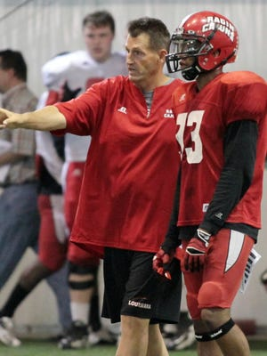 """UL assistant coach David Saunders, shown here giving instruction to UL defensive back Trevence Patt (33) in 2013, has left the Ragin' Cajuns coaching staff """"for personal reasons."""""""