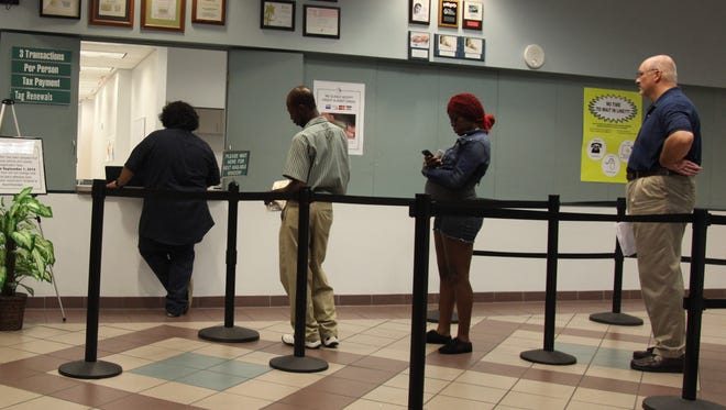 Visitors to the Lee County Tax Collector's Office stand in the tag renewal line.