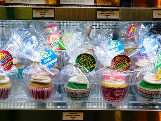 Assorted cupcakes are displayed for sale in celebration