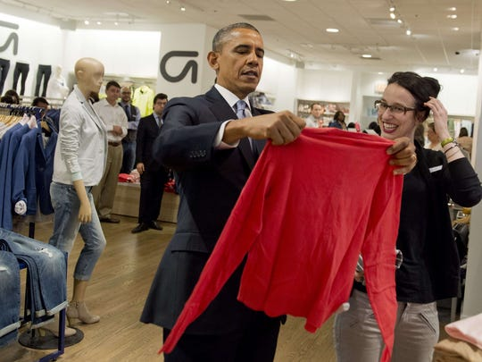 US President Barack Obama holds up a shirt as he shops for clothing for his family alongside store employee Susan Panariello during a visit to a Gap clothing store in New York City, March 11, 2014, to highlight his proposal to raise the federal minimum wage.