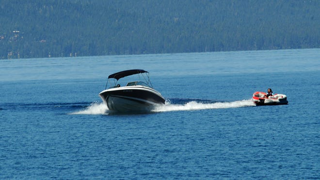A high speed boat pulls a woman on a flotation device on Lake Tahoe near Cave Rock Tuesday July 11, 2011.