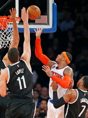 The Brooklyn Nets' Jerome Jordan (9) and Brook Lopez (11) defend Knicks forward Carmelo Anthony, who takes a shot Tuesday at Madison Square Garden.