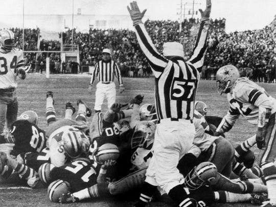 Green Bay Packers quarterback Bart Starr (15) digs his face across the goal line to score the winning touchdown against the Dallas Cowboys to bring the Packers their third consecutive NFL championship on Dec. 31, 1967, in the Ice Bowl.