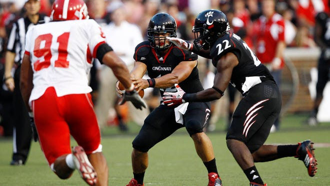 Bearcats quarterback Zach Collaros hands the ball off to running back Jameel Poteat in September of 2011.