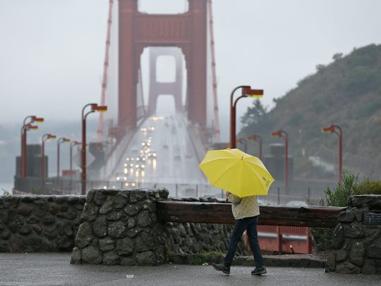 A woman walks in the rain at a vista point with the