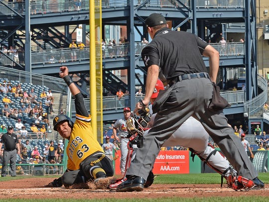 Chris Bostick slides in safely during a game last September against the Cardinals at PNC Park in Pittsburgh.