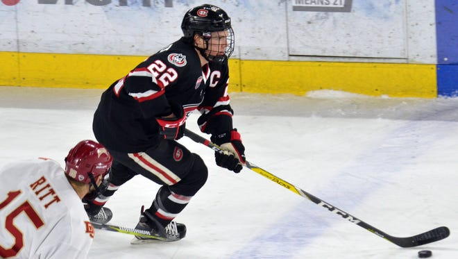 St. Cloud State's Jimmy Schuldt (22) carries the puck with Denver's Evan Ritt in pursuit Feb. 25 at Magness Arena in Denver. Schuldt was named an All-NCHC honorable mention pick this week.