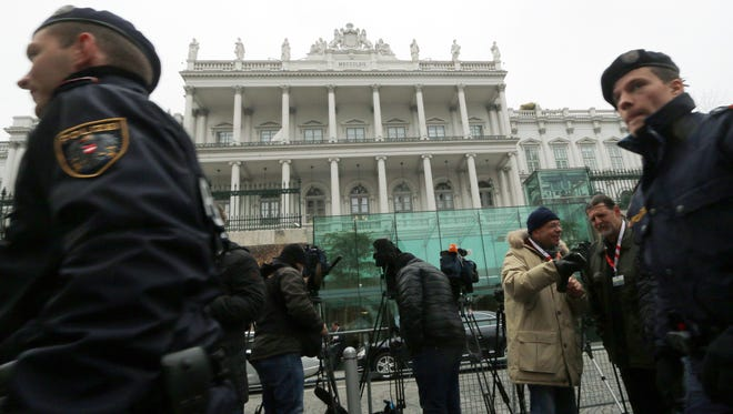 Police and journalists stand in front of Palais Coburg where closed-door nuclear talks with Iran take place in Vienna, Austria, Monday, Nov. 24, 2014.