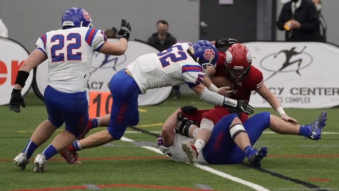 Lenawee Christian's Joey Breckel (bottom), Brandon Scott (52) and Nick Stuart (22) make a stop against a Suttons Bay player during the Division 1 8-Man state championship game Saturday.