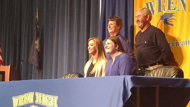 Madison King, left, and Ashley Collins react after signing their national letters of intent. In back are head coach Lynn Hicks, left, and assistant coach Shane Thompson.