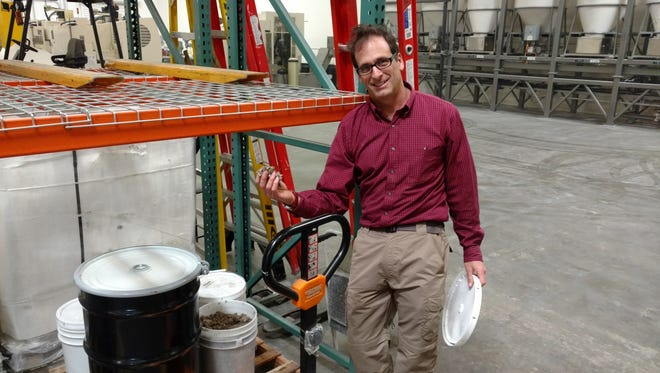 David Goldstein, Ventura County Recycling Market Development Zone administrator, holds waste paper fibers from Indy Containerboard in the Chamness warehouse. The larger drum in the picture contains discarded tissue fibers from Procter & Gamble.
